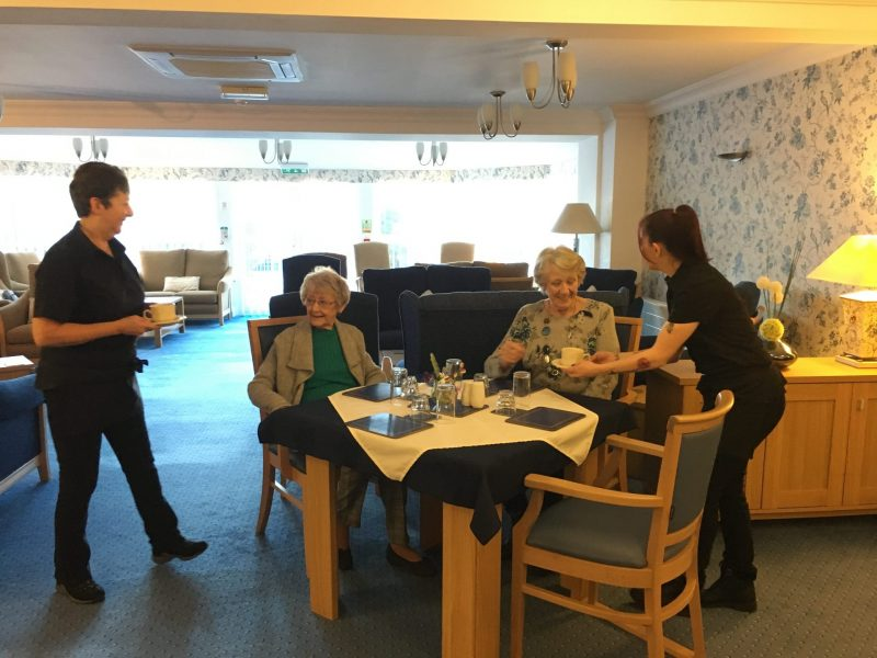 Residents being served lunch in the dining room